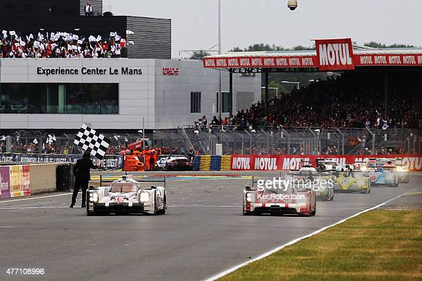 Nico Hulkenberg drives down the main straight in his Porsche Team 919 Hybrid to win Le Mans with team mates Earl Bamber and Nick Tandy alongside the...