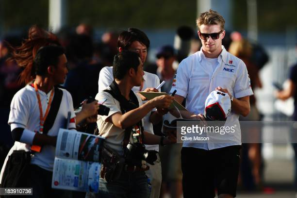 Nico Hulkenberg of Germany and Sauber F1 signs autographs for fans during previews for the Japanese Formula One Grand Prix at Suzuka Circuit on...