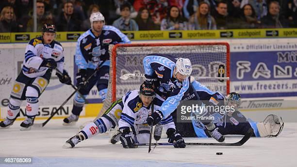 Nico Kraemmer of Hamburg challenges for the puck with Karl Stewart of Straubing during the DEL ice hockey match between Hamburg Freezers and...