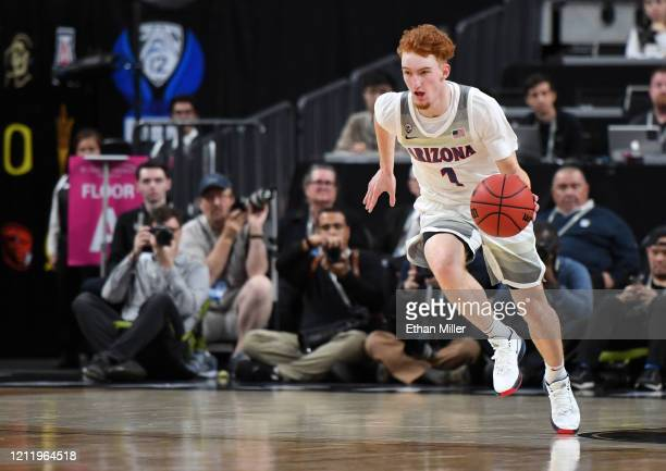 Nico Mannion of the Arizona Wildcats brings the ball up the court against the Washington Huskies during the first round of the Pac-12 Conference...