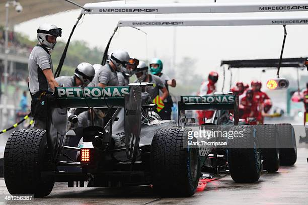 Nico Rosberg of Germany and Mercedes GP and Lewis Hamilton of Great Britain and Mercedes GP drive in for a pitstop during qualifying for the Malaysia...
