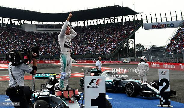 Nico Rosberg of Germany and Mercedes GP celebrates in Parc Ferme next to Lewis Hamilton of Great Britain and Mercedes GP after winning the Formula...