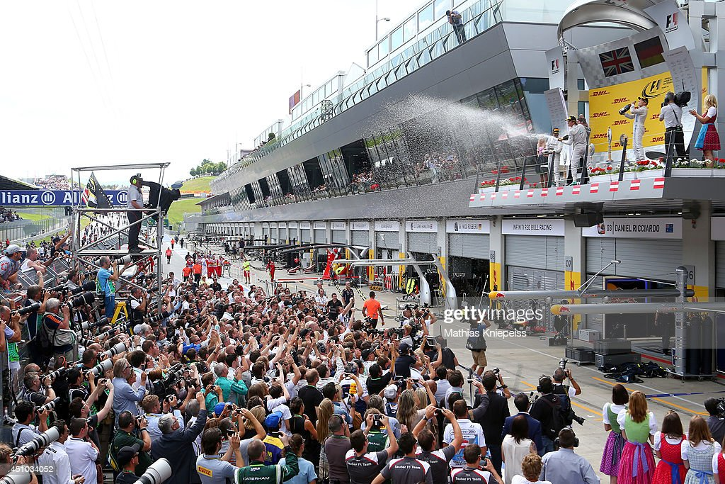 Nico Rosberg of Germany and Mercedes GP celebrates on the podium next to Lewis Hamilton of Great Britain and Mercedes GP and Valtteri Bottas of Finland and Williams after his victory in the Austrian Formula One Grand Prix at Red Bull Ring on June 22, 2014 in Spielberg, Austria.