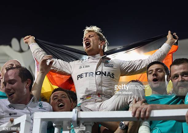 Nico Rosberg of Germany and Mercedes GP celebrates with his team after finishing second and securing the F1 World Drivers Championship during the Abu...