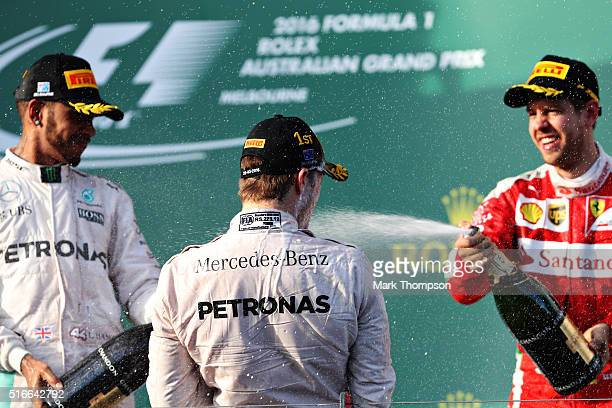 Nico Rosberg of Germany and Mercedes GP gets sprayed with champagne by Sebastian Vettel of Germany while Lewis Hamilton of Great Britain and Mercedes...