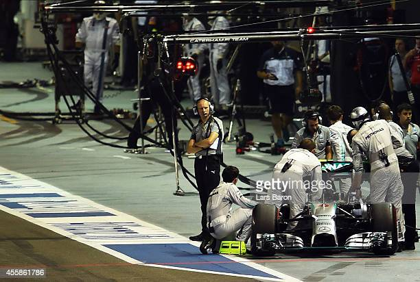 Nico Rosberg of Germany and Mercedes GP is pushed back to the garage during the formation lap after experiencing problems before the Singapore...