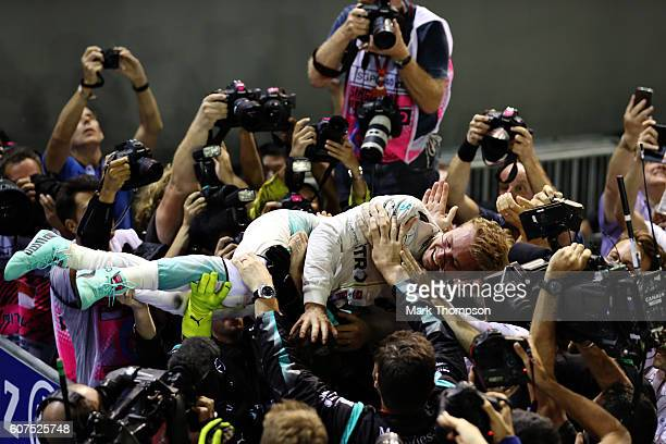 Nico Rosberg of Germany and Mercedes GP jumps on his team to celebrate his win in parc ferme during the Formula One Grand Prix of Singapore at Marina...