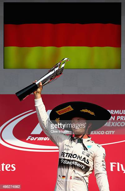 Nico Rosberg of Germany and Mercedes GP lifts the trophy as he celebrates on the podium after winning the Formula One Grand Prix of Mexico at...