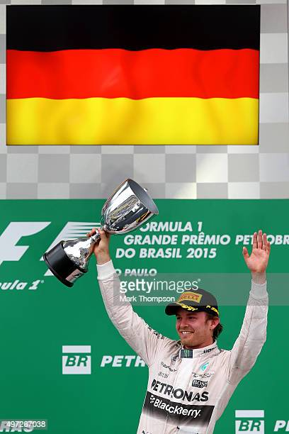 Nico Rosberg of Germany and Mercedes GP lifts the trophy on the podium as he celebrates winning the Formula One Grand Prix of Brazil at Autodromo...