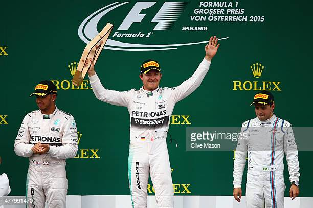 Nico Rosberg of Germany and Mercedes GP lifts the trophy on the podium next to Lewis Hamilton of Great Britain and Mercedes GP and Felipe Massa of...