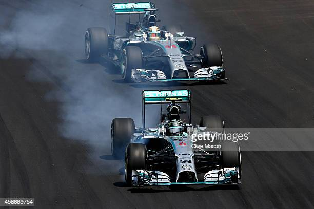 Nico Rosberg of Germany and Mercedes GP locks up in front of Lewis Hamilton of Great Britain and Mercedes GP during the Brazilian Formula One Grand...