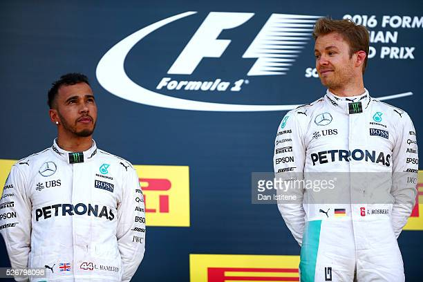 Nico Rosberg of Germany and Mercedes GP looks at his teammate Lewis Hamilton of Great Britain and Mercedes GP as he celebrates his win on the podium...