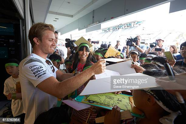 Nico Rosberg of Germany and Mercedes GP signs autographs for fans during previews ahead of the Formula One Grand Prix of Japan at Suzuka Circuit on...