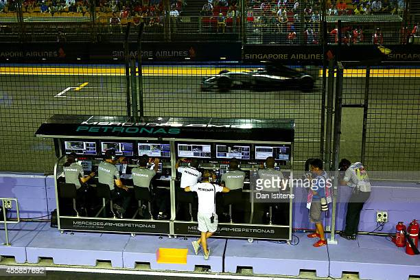 Nico Rosberg of Germany and Mercedes GP stand with the team on the pit wall as Lewis Hamilton of Great Britain and Mercedes GP drives by during the...