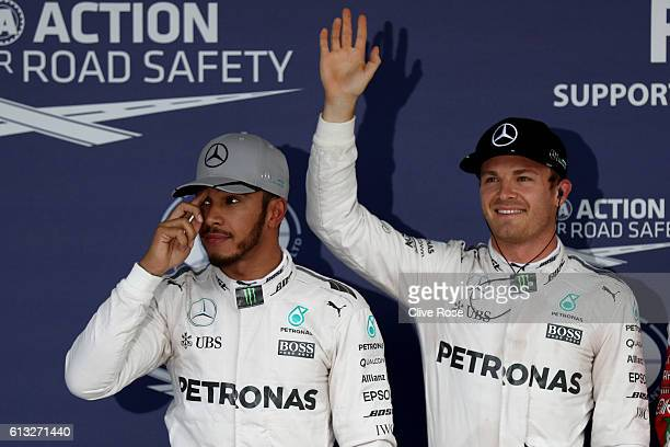 Nico Rosberg of Germany and Mercedes GP waves to the crowd from parc ferme after qualifying in pole position Lewis Hamilton of Great Britain and...