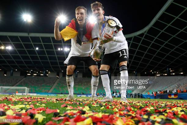 Nico Schlotterbeck and Mergim Berisha of Germany celebrate with the UEFA European Under-21 Championship trophy following victory in the 2021 UEFA...