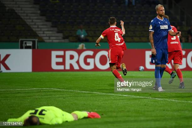 Nico Schlotterbeck of Berlin celebrates his team's first goal af goalkeeper Marius Gersbeck of Karlsruhe reacts during the DFB Cup first round match...