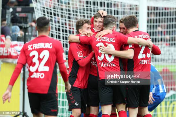 Nico Schlotterbeck of Freiburg celebrates with teammates after scoring his team's second goal during the Bundesliga match between Sport-Club Freiburg...
