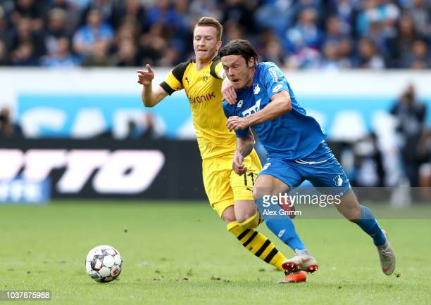 Nico Schulz of 1899 Hoffenheim is challenged by Marco Reus of Borussia Dortmund during the Bundesliga match between TSG 1899 Hoffenheim and Borussia...
