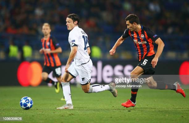 Nico Schulz of 1899 Hoffenheim runs with the ball under pressure from Taras Stepanenko of Shakhtar Donetsk during the Group F match of the UEFA...