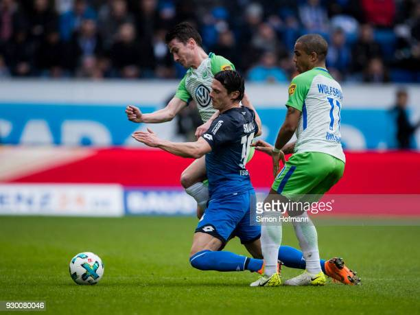 Nico Schulz of Hoffenheim is challenged by Paul Verhaegh of Wolfsburg and Daniel Didavi of Wolfsburg during the Bundesliga match between TSG 1899...