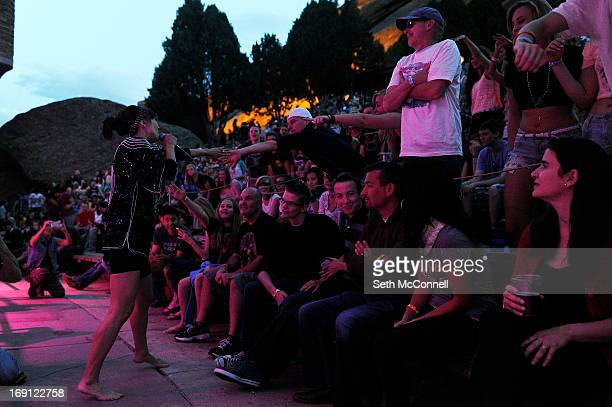 Nico Vega vocalist Aja Volkman shakes hands with audience members while performing at Red Rocks Amphitheatre on May 16 2013 in Morrison Colorado