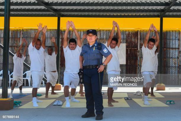 Nicol Gomez guardian at the La Esperanza prison poses for a portrait with a group of prisoners practicing yoga in San Salvador on March 4 2018 In the...