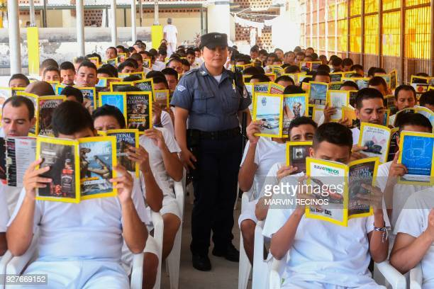 TOPSHOT Nicol Gomez guardian at the La Esperanza prison poses for a portrait with a group of prisoners reading in San Salvador on March 4 2018 / AFP...