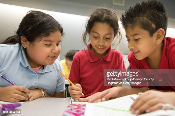 Nicol Lobato left and Carlos Arca helps Sury Villegas with homework during an after school junior coaches meeting at Garfield elementary School in...