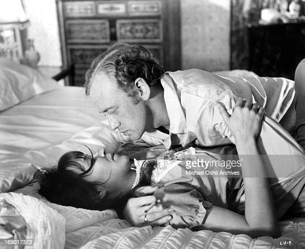 Nicol Williamson on top on Anna Karina and passionately looking into her eyes in a scene from the film 'Laughter in the Dark' 1969