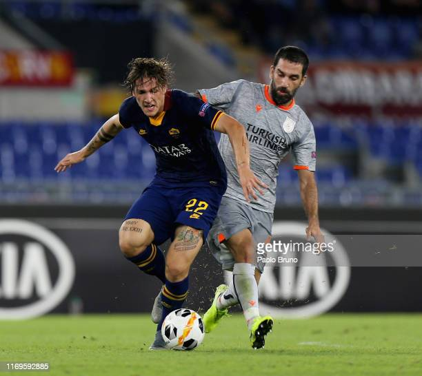 Nicolò Zaniolo of AS Roma competes for the ball with Arda Turan of Istanbul Basaksehir F.K. During the UEFA Europa League group J match between AS...