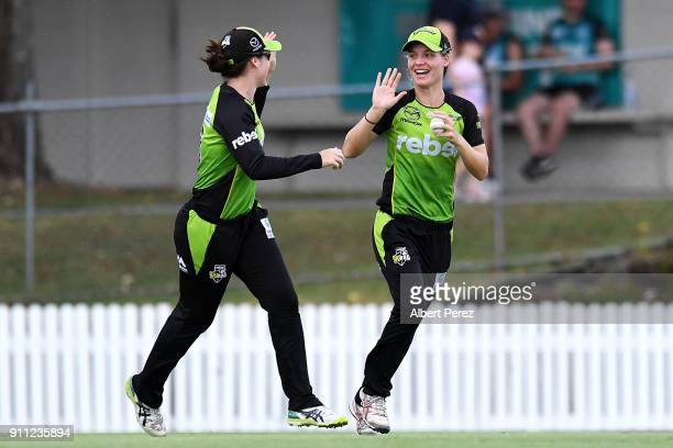 Nicola Carey of the Thunder celebrates with team mates after catching Beth Mooney of the Heat during the Women's Big Bash League match between the...