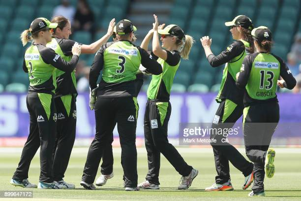 Nicola Carey of the Thunder celebrates with team mates after taking a catch to dismiss Lauren Winfield of the Hurricanes during the Women's Big Bash...