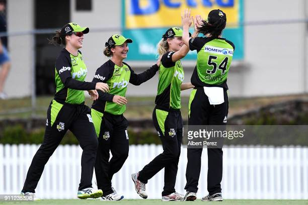 Nicola Carey of the Thunder is congratulated by team mates after catching Beth Mooney of the Heat during the Women's Big Bash League match between...