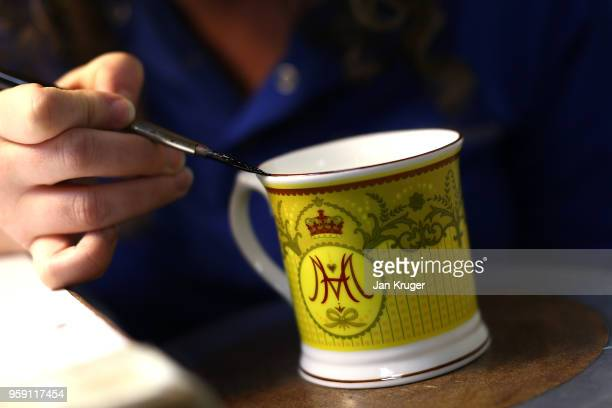 Nicola Gilchrist applies gilding to a cup as part of a special collection ahead of the wedding of Prince Harry and Meghan Markle at William Edwards...