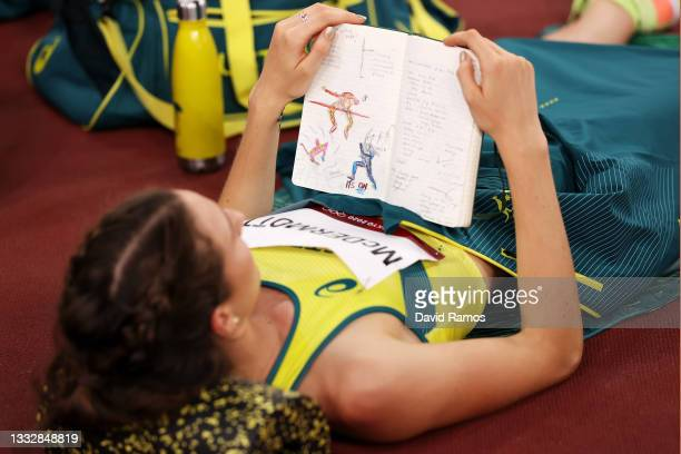 Nicola McDermott of Team Australia reads her journal as she competes in the Women's High Jump Final on day fifteen of the Tokyo 2020 Olympic Games at...