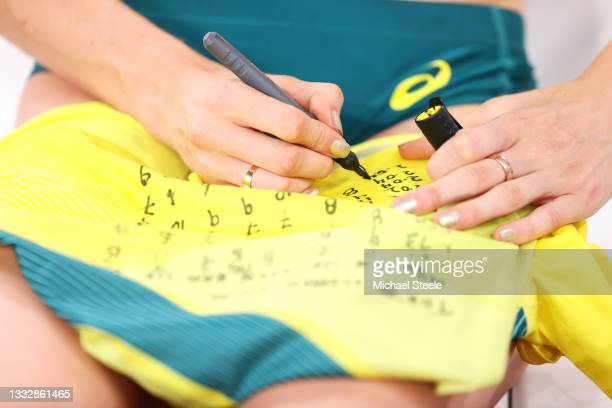 Nicola McDermott of Team Australia writes on her shirt during the Women's High Jump Final on day fifteen of the Tokyo 2020 Olympic Games at Olympic...