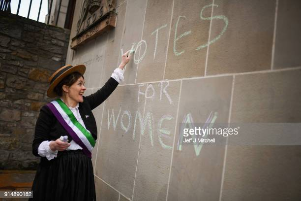 Nicola Wright dressed in Suffragettes costume holds a mock protest on the Royal Mile on February 6 2018 in Edinburgh Scotland The event was held to...