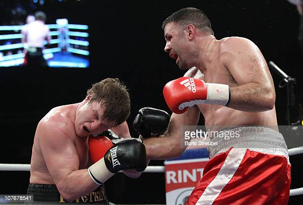 Nicolai Firtha of USA and Alexander Povetkin of Russia exchange punches during their Heavyweight fight at MaxSchmeling Hall on December 18 2010 in...