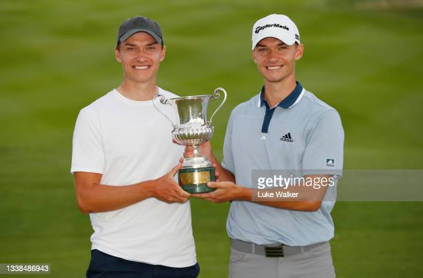Nicolai Hojgaard of Denmark poses for a photo with his brother Ramus Hojgaard of Denmark and the trophy during Day Four of The Italian Open at Marco...