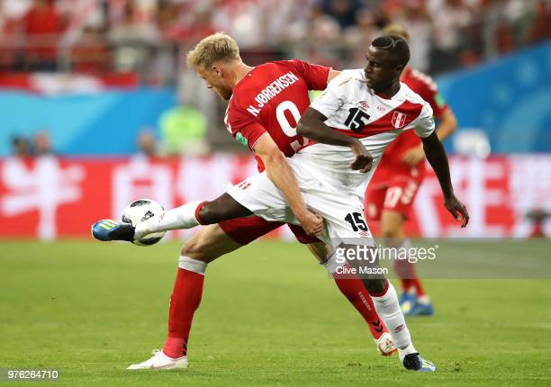 Nicolai Jorgensen of Denmark is tackled by Christian Ramos of Peru during the 2018 FIFA World Cup Russia group C match between Peru and Denmark at...