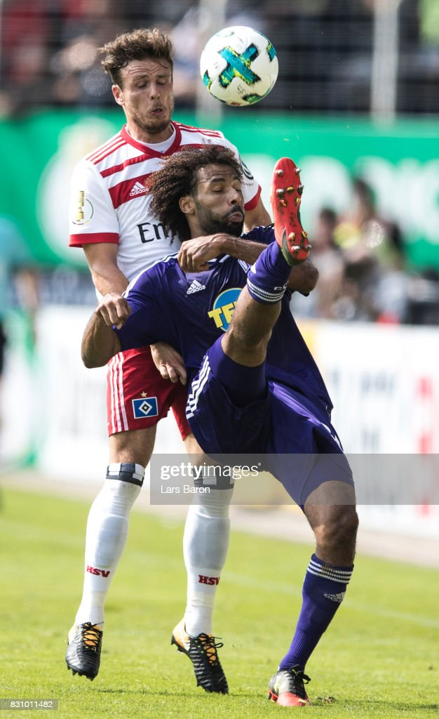 Nicolai Mueller of Hamburg challenges Nazim Sangare of Osnabrueck during the DFB Cup match between VfL Osnabrueck and Hamburger SV at Osnatel Arena on August 13, 2017 in Osnabrueck, Germany.