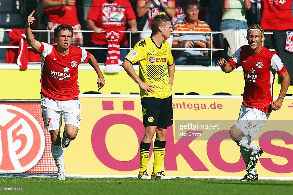 Nicolai Mueller (L) of Mainz celebrates his team's first goal with team mate Marcel Risse (R) as Lukasz Piszczek (C) of Dortmund reacts during the Bundesliga match between FSV Mainz 05 and Borussia Dortmund at Coface Arena on September 24, 2011 in Mainz, Germany.
