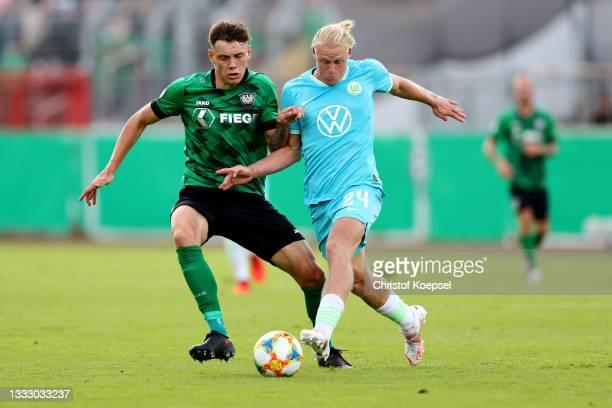 Nicolai Remberg of Muenster challenges Xaver Schlager of Wolfsburg during the DFB Cup first round match between Preußen Münster and VfL Wolfsburg at...