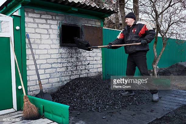 Nicolai shovels coal outside his house on February 5 2015 in Grabovo Ukraine The unemployed coal miner helped to recover remains of the MH17...