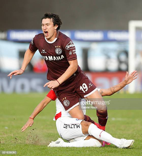 Nicola‡s Aguirre of Lanus is fouled by Cristian Ledesma of Argentinos Juniors during a match between Argentinos Juniors and Lanus as part of Torneo...