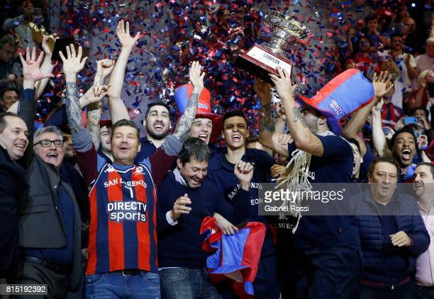 Nicolas Aguirre of San Lorenzo lifts the trophy to celebrate with teammates after winning the fifth game between San Lorenzo and Regatas as part of...