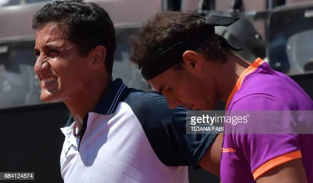 Nicolas Almagro of Spain grimaces after an injury as Rafael Nadal of Spain looks on during their match at the ATP Tennis Open tournament on May 17...