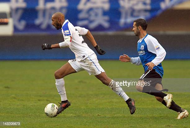 Nicolas Anelka newly named playercoach for Shanghai Shenhua vies with a Dalian Shide player in Dalian northeast China's Liaoning province on April 21...