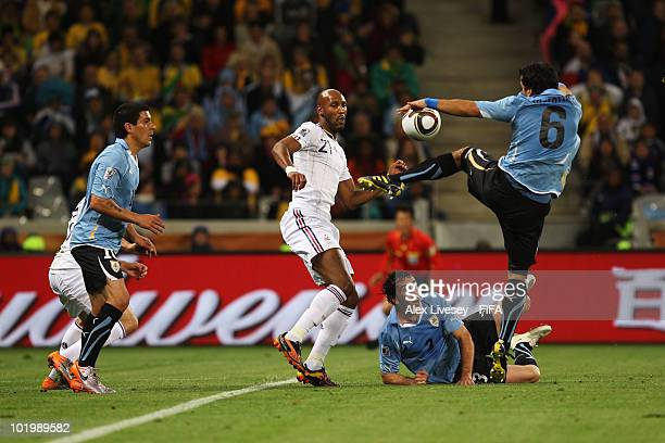 Nicolas Anelka of France tries to score against Mauricio Victorino of Uruguay while Diego Godin of Uruguay looks on during the 2010 FIFA World Cup...
